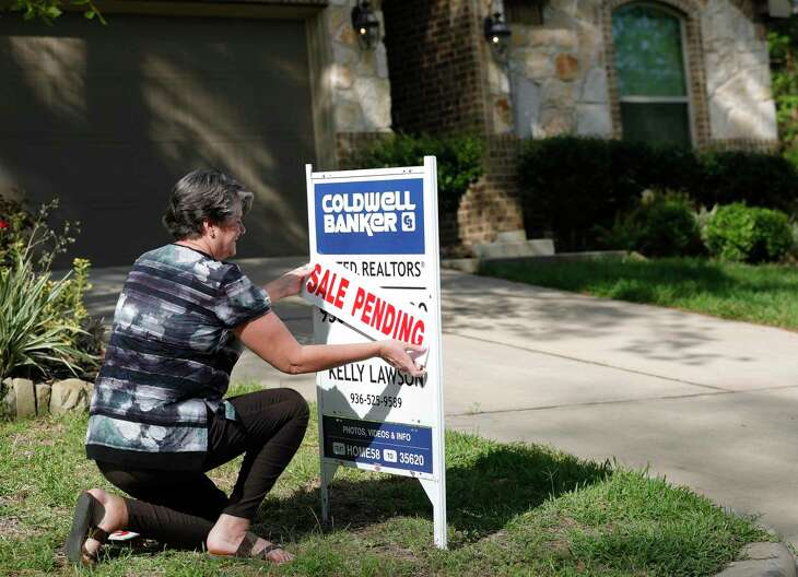 Realtor Kelly Lawson attaches a sale pending sign in front of a home, Friday, March 27, 2020, in Willis.