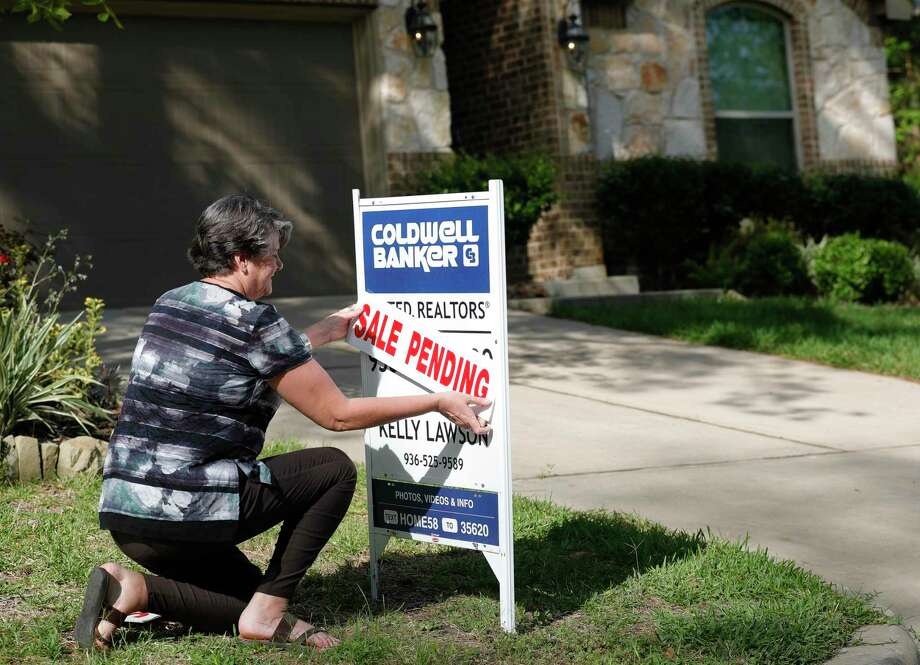 Realtor Kelly Lawson attaches a sale pending sign in front of a home, Friday, March 27, 2020, in Willis. Photo: Jason Fochtman, Houston Chronicle / Staff Photographer / 2020 © Houston Chronicle