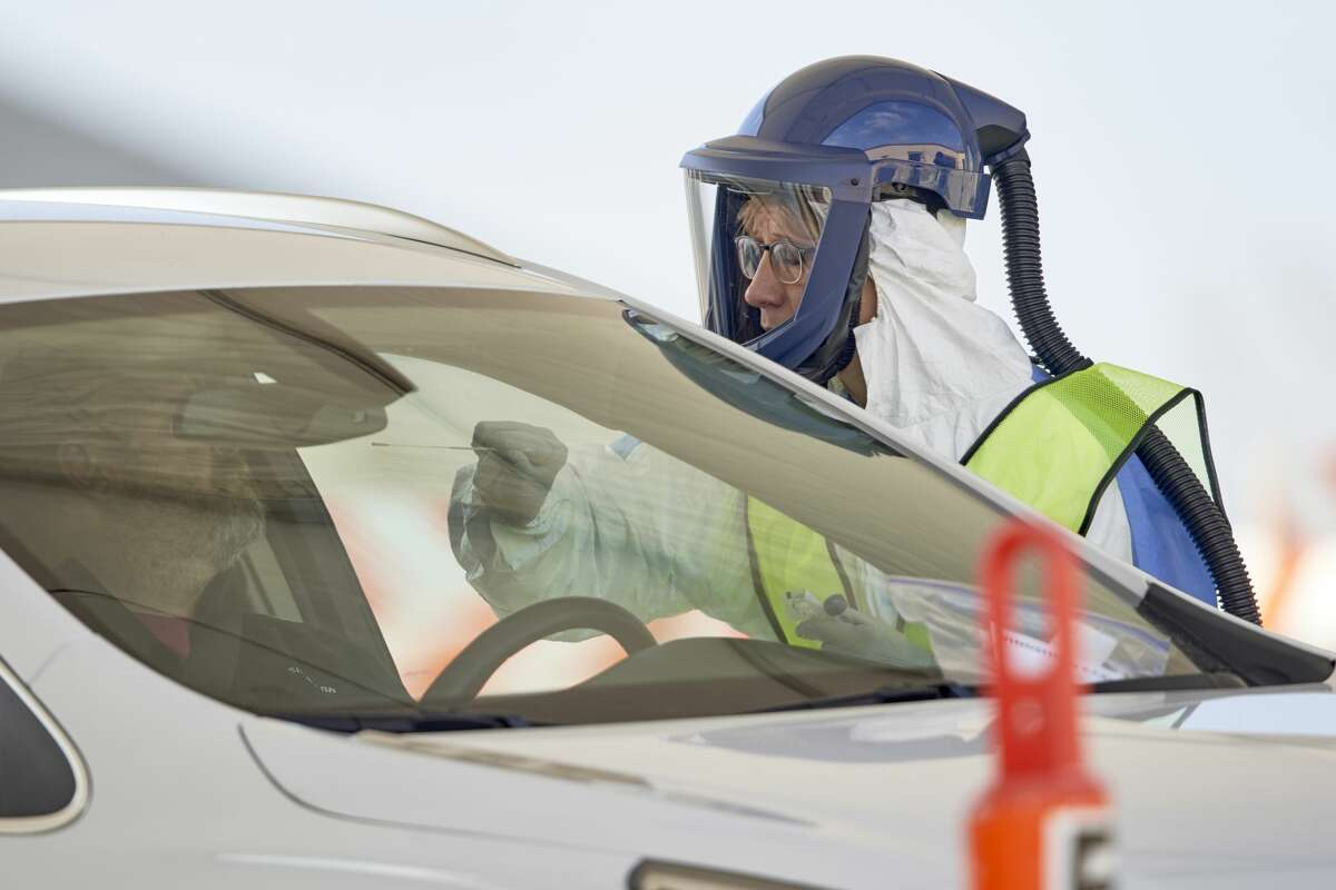 A nurse in protective gear tests for the COVID-19 and coronavirus virus at a drive-thru test location at Bryant Health's LifePointe campus in Lincoln, Neb., Tuesday, March 24, 2020. Testing was by appointment only.
