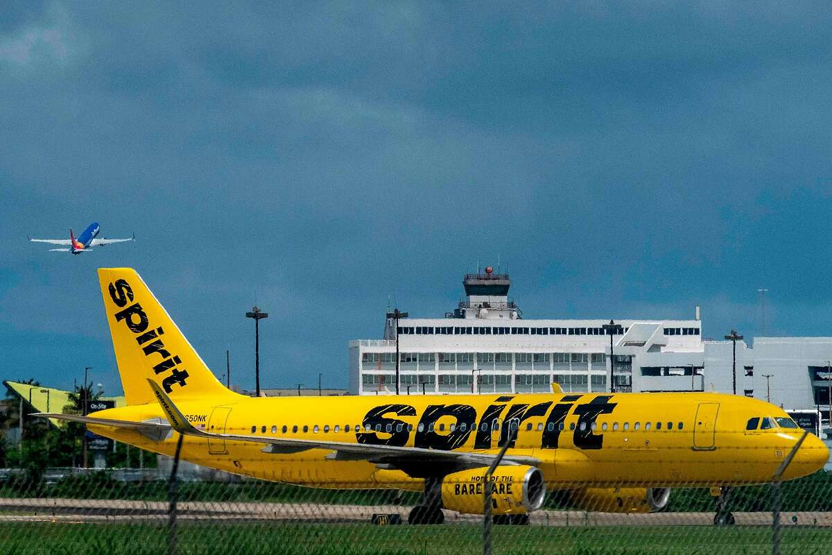 A Spirit Airlines commercial airplane is seen taxing on the tarmac as another plane takes off from the Luis Munoz Marin International Airport in San Juan, Puerto Rico, on March 18, 2020.