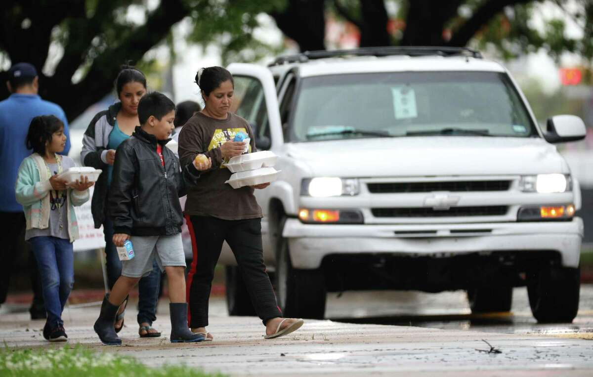 In this March 20 file photo, people leave Aldine ISD's MacArthur High School after picking up student lunches. Aldine ISD ended daily meal pickup this week, shifting instead to providing three days' worth of meals on Mondays and Thursdays.