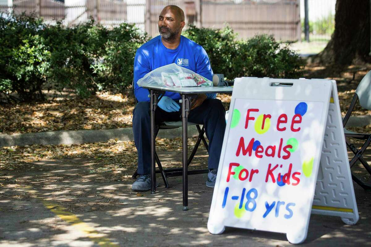 In this March 27 file photo, Tim Singleton, director of the Houston Parks and Recreation Department's Woodland Community Center, sits in the center's parking lot while offering free lunches for children. The department reported providing about 1,350 lunches on Thursday and 1,770 lunches on Friday, the first two days that Houston ISD did not offer curbside food pickup.