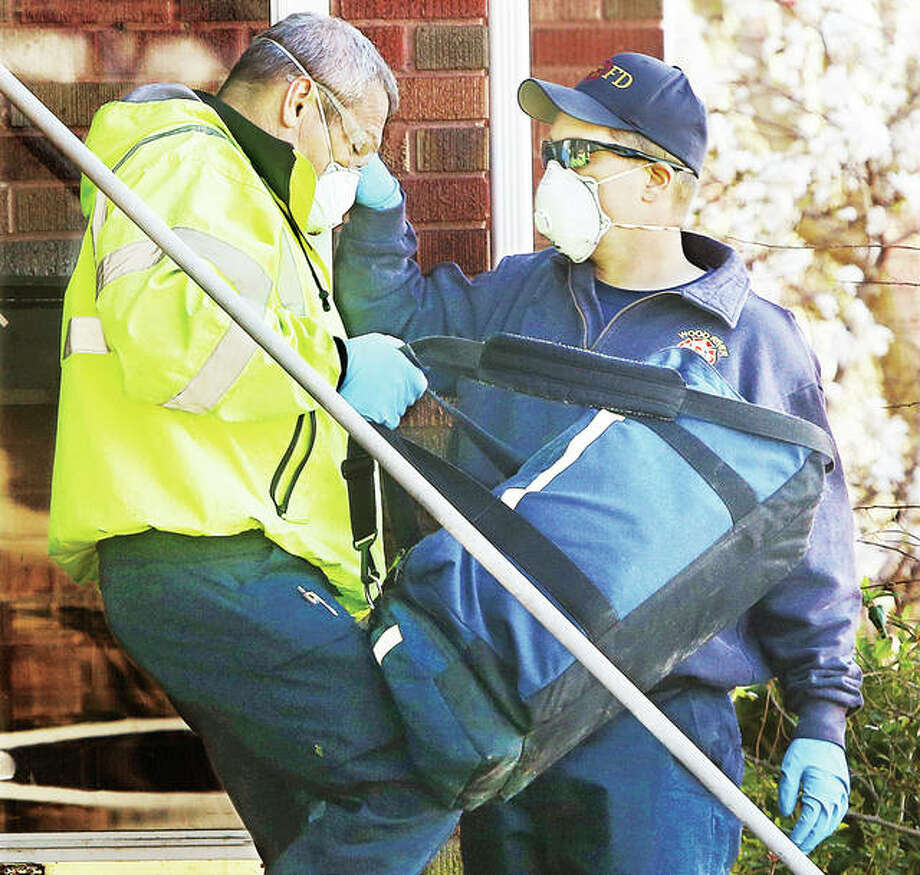 """Unable to avoid contact, or stay six-feet-away, local paramedics and firefighters have become the front line of heroism in the United States today. While others are following """"stay at home"""" rules they are rushing to help the most likely among us who could be infected with the COVID-19 virus. Two Wood River firefighters exit a house Monday to meet ambulance paramedics where a subject inside was having shortness of breath after reportedly recently running a fever. President Trump said Monday he was considering some type of """"hazard pay"""" for first responders across the nation, perhaps in a future aid package. Photo: John Badman   The Telegraph"""