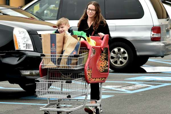 Angela Hunt, who was quarantined as an unconfirmed case of coronavirus but has been cleared to resume her life by the East Shore District Health Department, returns to her car Monday after going grocery shopping at the Big Y Supermarket in Branford with her son Vincent Hunt, 6.