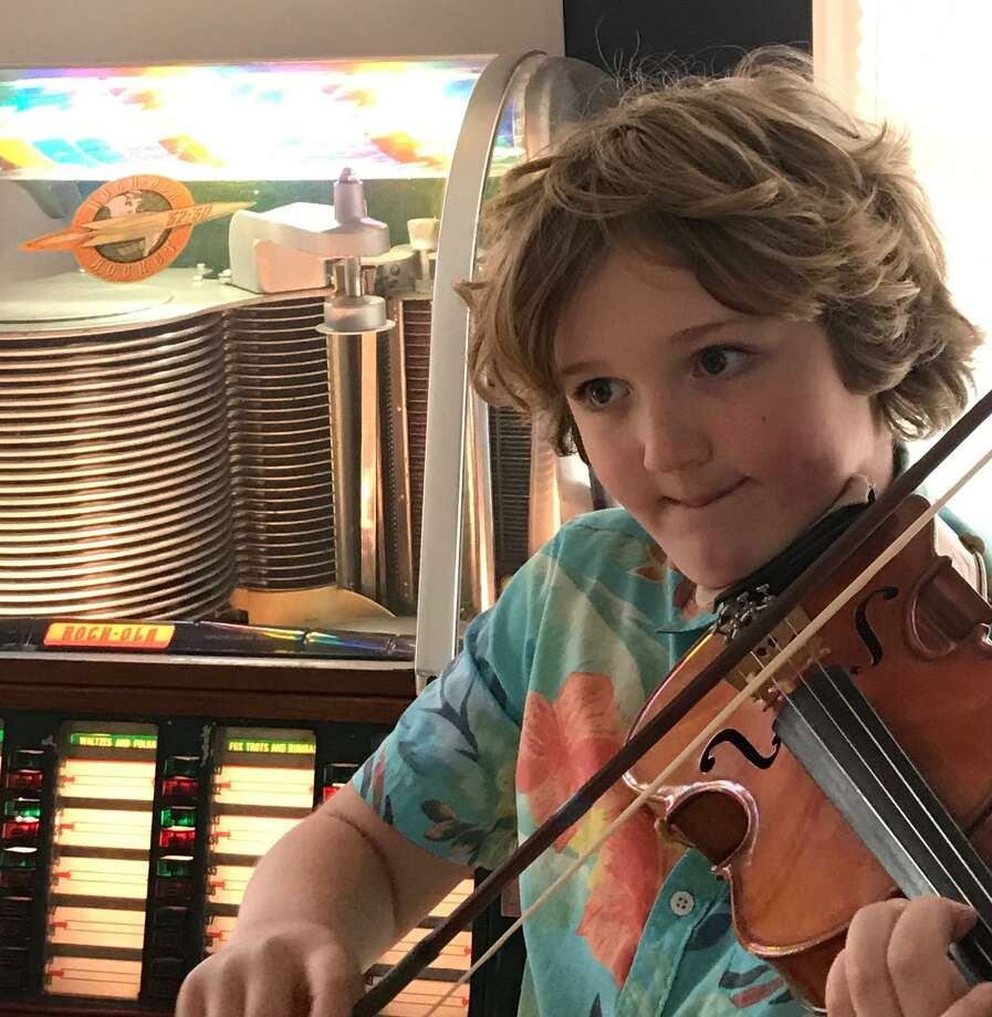 Nine-year-old Ridgefielder Austin Wakin is traveling to people's homes to play Happy Birthday, outside, on his violin. Photo: Contributed Photo / Alysa Wakin