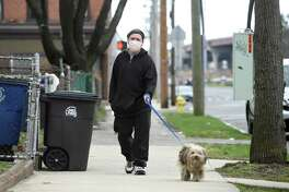 Wearing a face mask, Robert Lopez walks his dog Peanut on James Street in New Haven Monday.