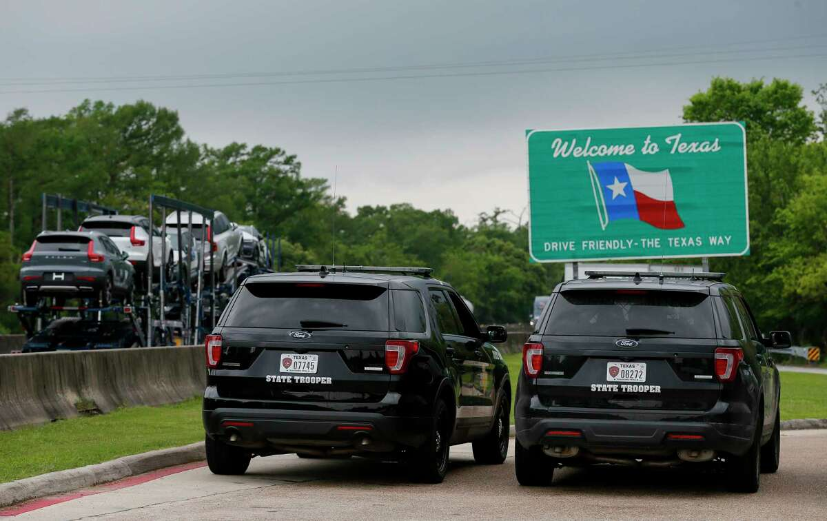Texas Highway Patrol troopers are seen parked at the Texas Travel Information Center, along the Interstate 10 Highway westbound lanes Monday, March 30, 2020, in Orange, Texas. Gov. Greg Abbott on Sunday tightened travel to Texas, ordering some motorists from Louisiana to self-quarantine for two weeks. The new restrictions were effective Monday at noon, and DPS said they will not be establishing checkpoints at this time.