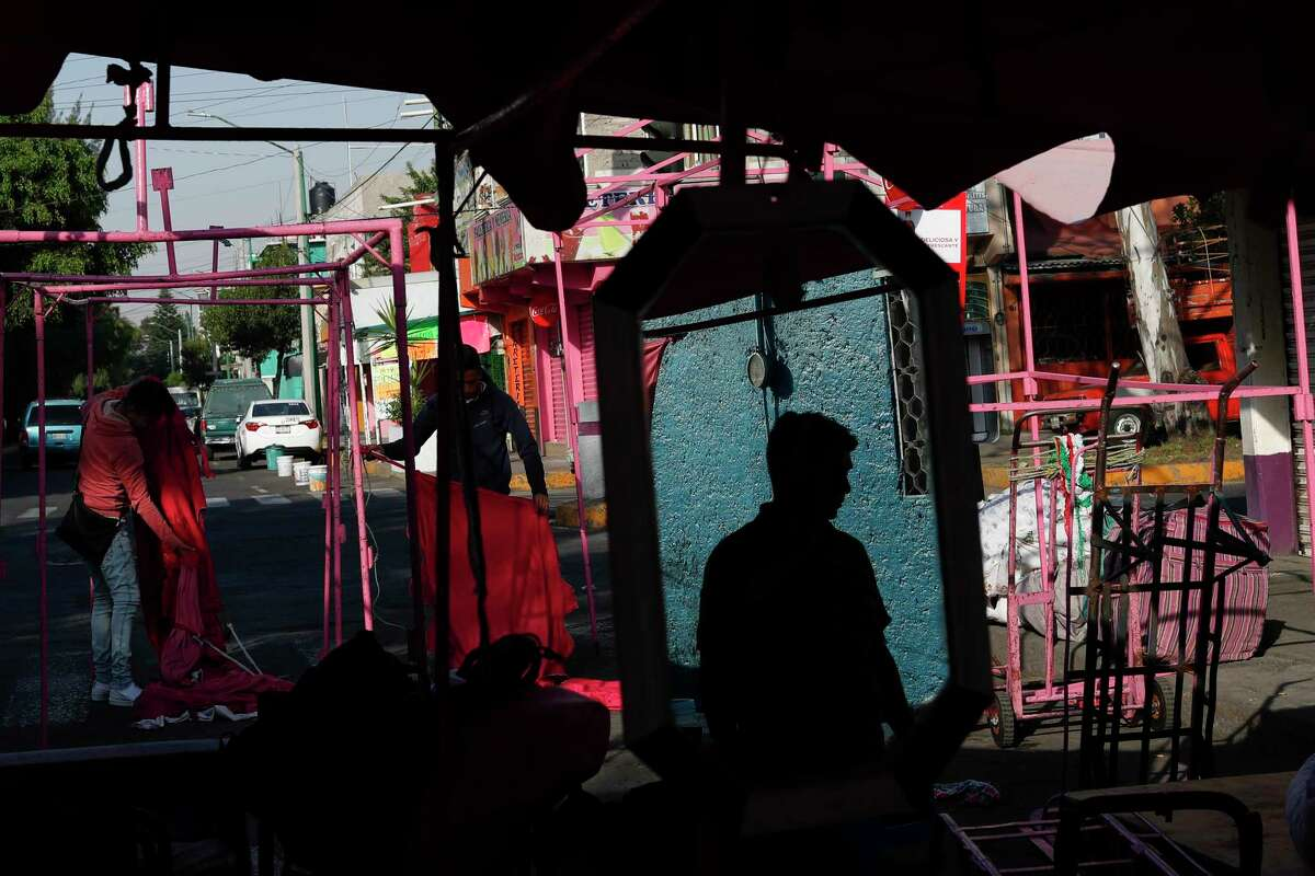 A man is reflected in a mirror as vendors set up their stalls at the start of the day in a street market in Mexico City, Saturday, March 28, 2020, as business is reduced amid the spread of the new coronavirus.