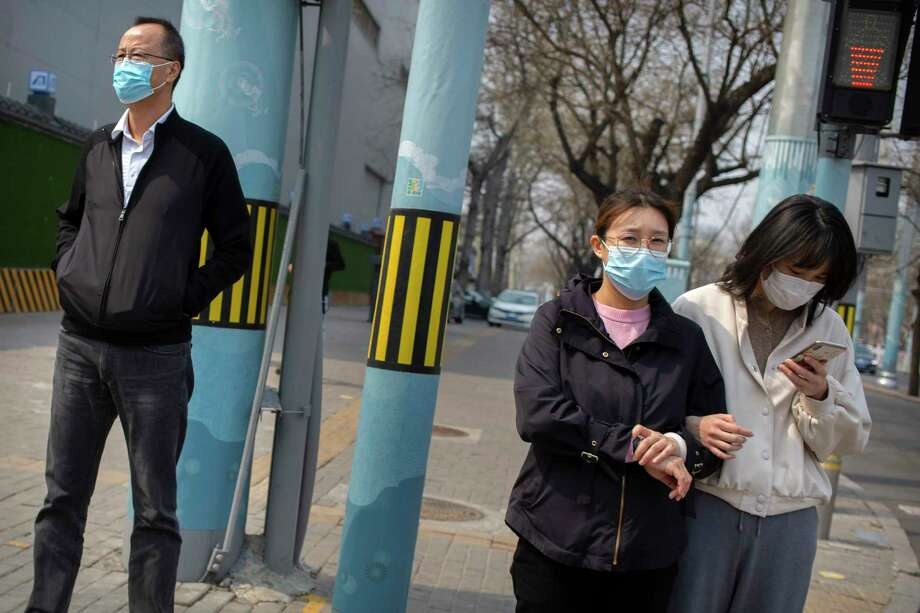 People wearing face masks wait to cross a street in Beijing on March 31, 2020. The U.S. Centers for Disease Control and Prevention reportedly is considering its guidance on face mask use. Its current recommendation is that people who are well should not wear them in public. Photo: Mark Schiefelbein, AP / Copyright 2020 The Associated Press. All rights reserved