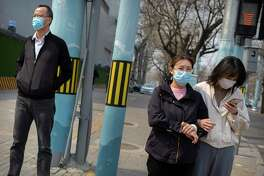 People wearing face masks wait to cross a street in Beijing, Tuesday, March 31, 2020. China on Tuesday reported just one new death from the coronavirus and a few dozen new cases, all brought from overseas.