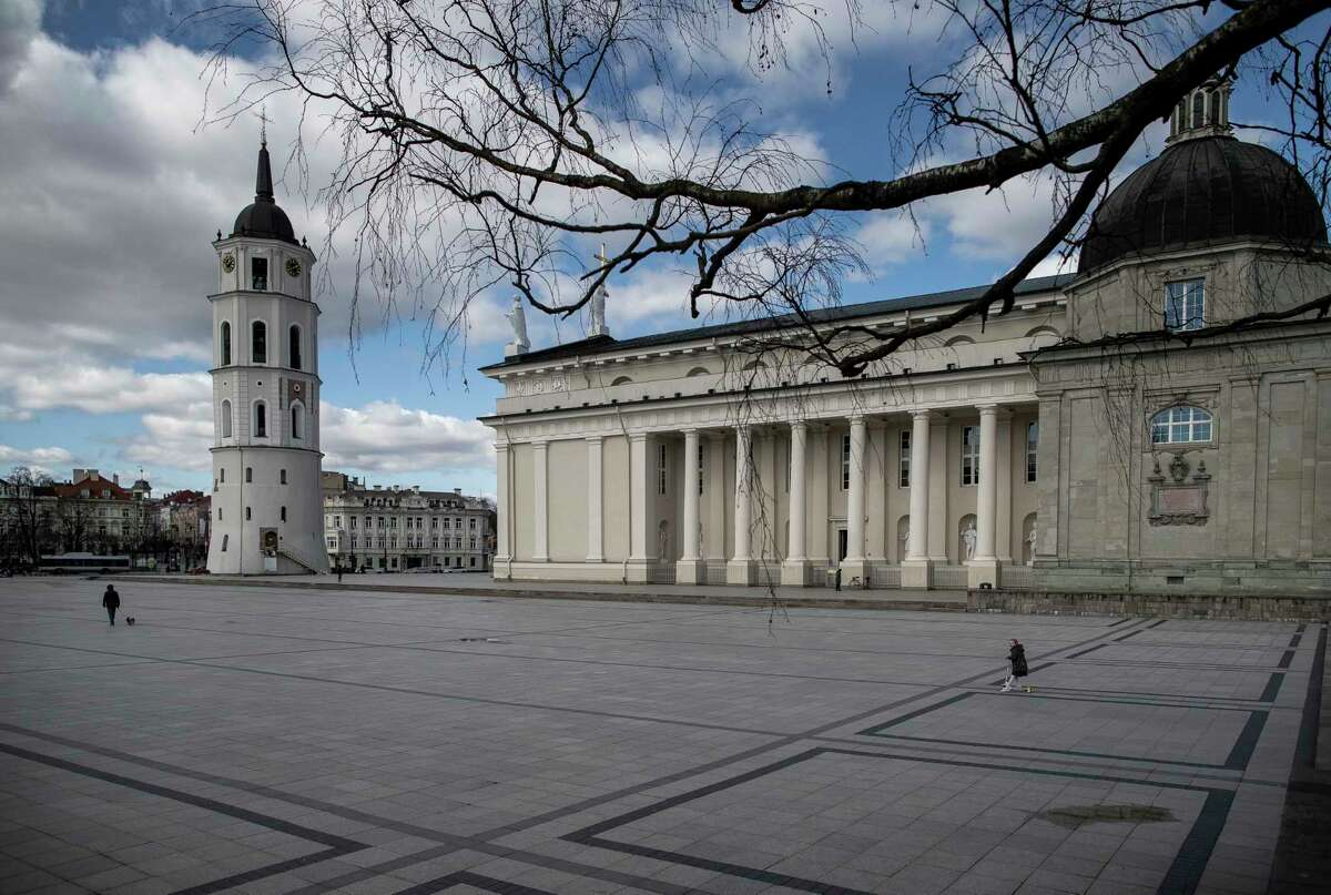 A girl rides a scooter through empty Cathedral square in Vilnius, Lithuania, Saturday, March 21, 2020.