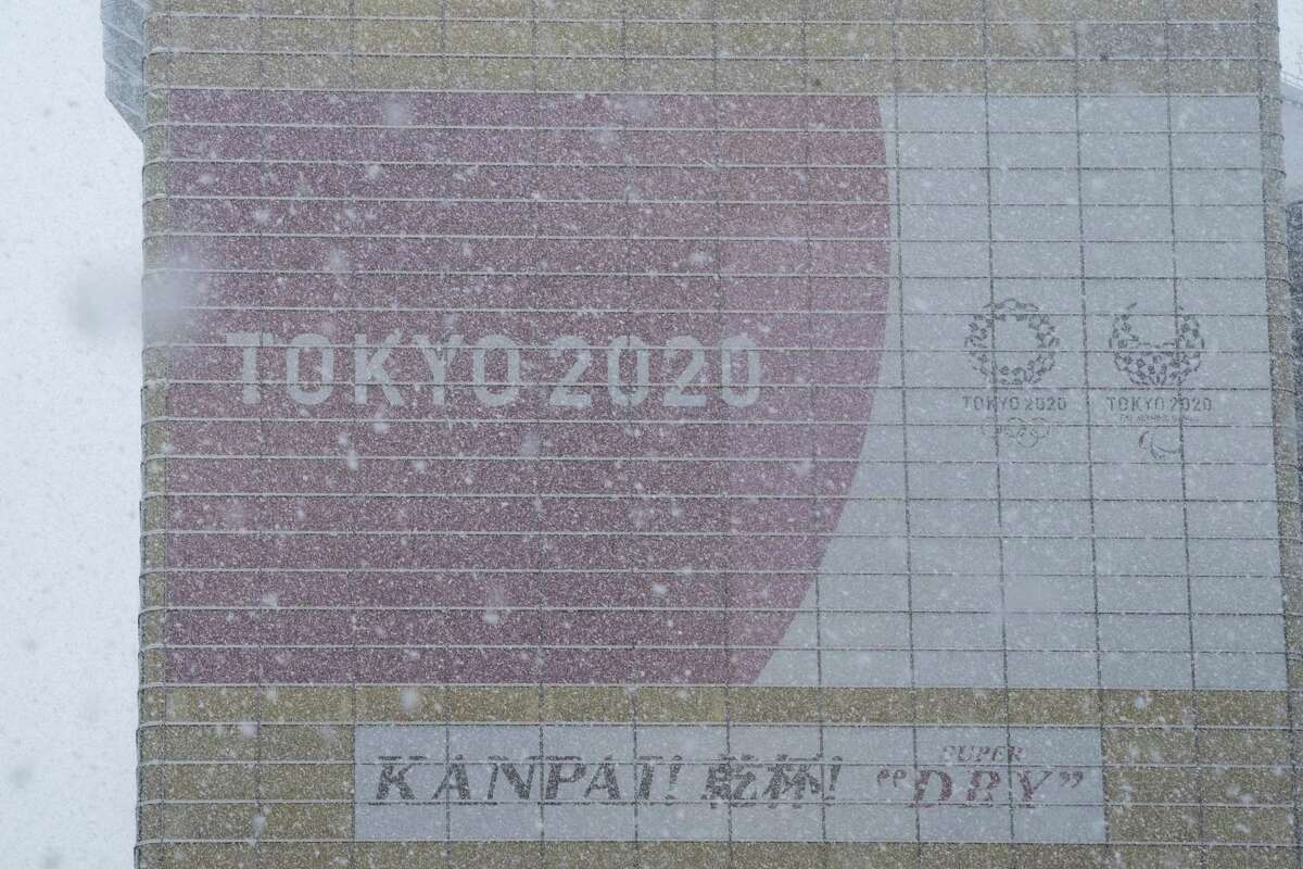 Snow falls as an advertisement of the Tokyo 2020 Olympic and Paralympic Games is seen on the facade of a building in the Asakusa district on March 29, 2020 in Tokyo, Japan. Tokyo Governor Yuriko Koike has requested the city's residents to stay at home this weekend while numerous parks and businesses including some shops, cafes and cinemas have been told to close amid concern over the recent increase in COVID-19 cases.