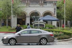 A person is stopped by security and an officer with the Montgomery County Sheriff's Office at the entrance of The Conservatory at Alden Bridge after 12 residents tested positive for coronavirus, Tuesday, March 31, 2020, in The Woodlands. On Monday, Montgomery County Judge Mark Keough issued a shelter-in-place order for residents of the senior living community that offers apartment homes for up to 237 residents.