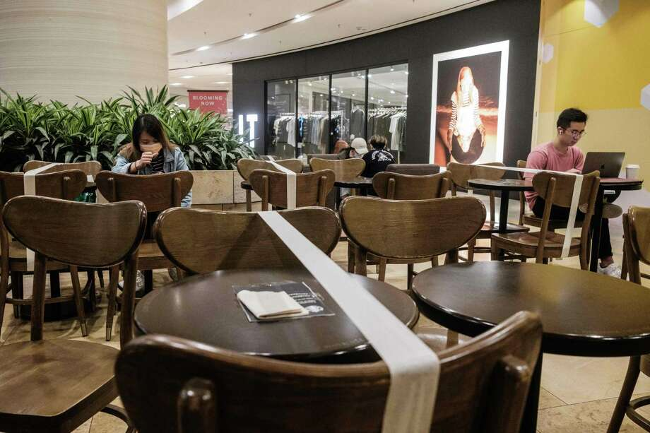 Customers sit in a cafe where social distancing between patrons has been enforced by placing white tape over unavailable tables and chairs as a precautionary measure against the COVID-19 coronavirus. Photo: ANTHONY WALLACE, Contributor / AFP Via Getty Images / AFP or licensors