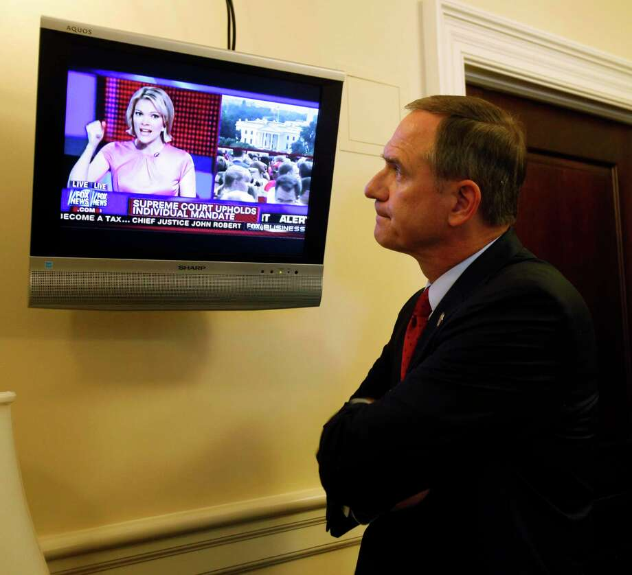 Del. Richard L. Anderson, R-Prince William reacts to the news that the Supreme Court upheld the Obama healthcare reform law from Megyn Kelly, America Live anchor on the Fox News channel, as he watches in the Virginia State Capitol in Richmond, Va. Thursday, June 28, 2012. (AP Photo/Richmond Times-Dispatch, Bob Brown). Photo: BOB BROWN / Associated Press / RICHMOND TIMES-DISPATCH