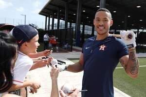 El puertorriqueño Carlos Correa (der.) firma autógrafos a los aficionados durante la reciente pretemporada de los Astros de Houston en Florida.