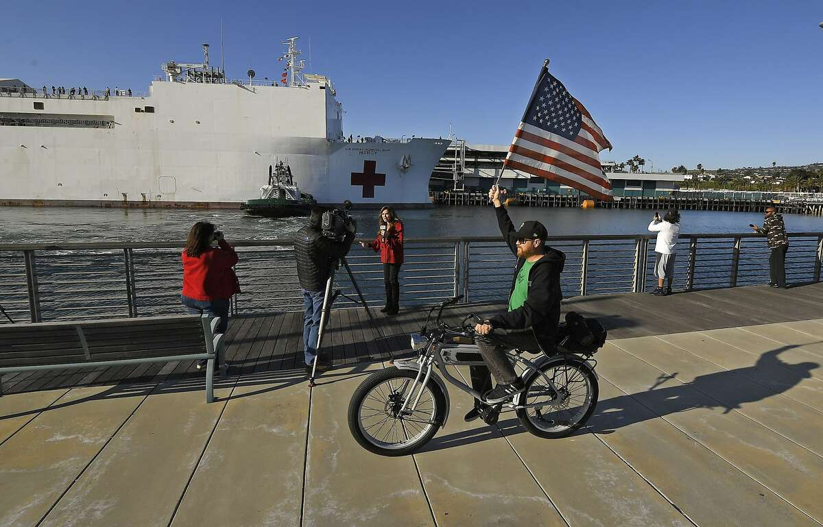 A cyclist rides with an American flag as the USNS Mercy docks at the Port of Los Angeles, Friday, March 27, 2020, in Los Angeles. The The 1,000-bed Navy hospital ship is expected to help take the load off Los Angeles area hospitals as they treat coronavirus patients. The new coronavirus causes mild or moderate symptoms for most people, but for some, especially older adults and people with existing health problems, it can cause more severe illness or death. (AP Photo/Mark J. Terrill)