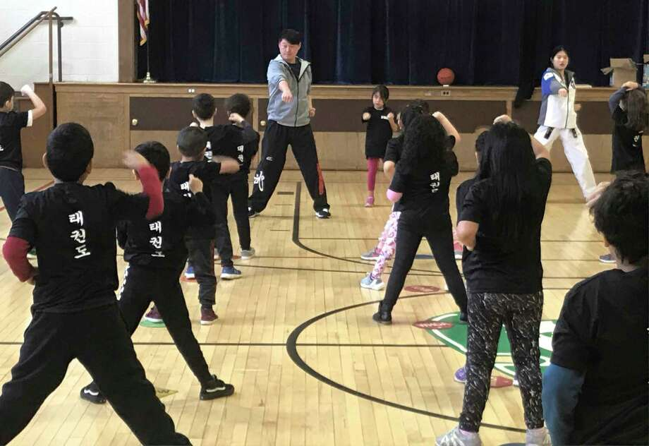 First-graders at Park Avenue Elementary School earned their white belts after completing a taekwondo program to combat bullying with Taekwondo instructor Master Kris Hyun from the Master Kris Foundation in Brookfield, CT. Photo: Contributed Photo / The News-Times / The News-Times Contributed