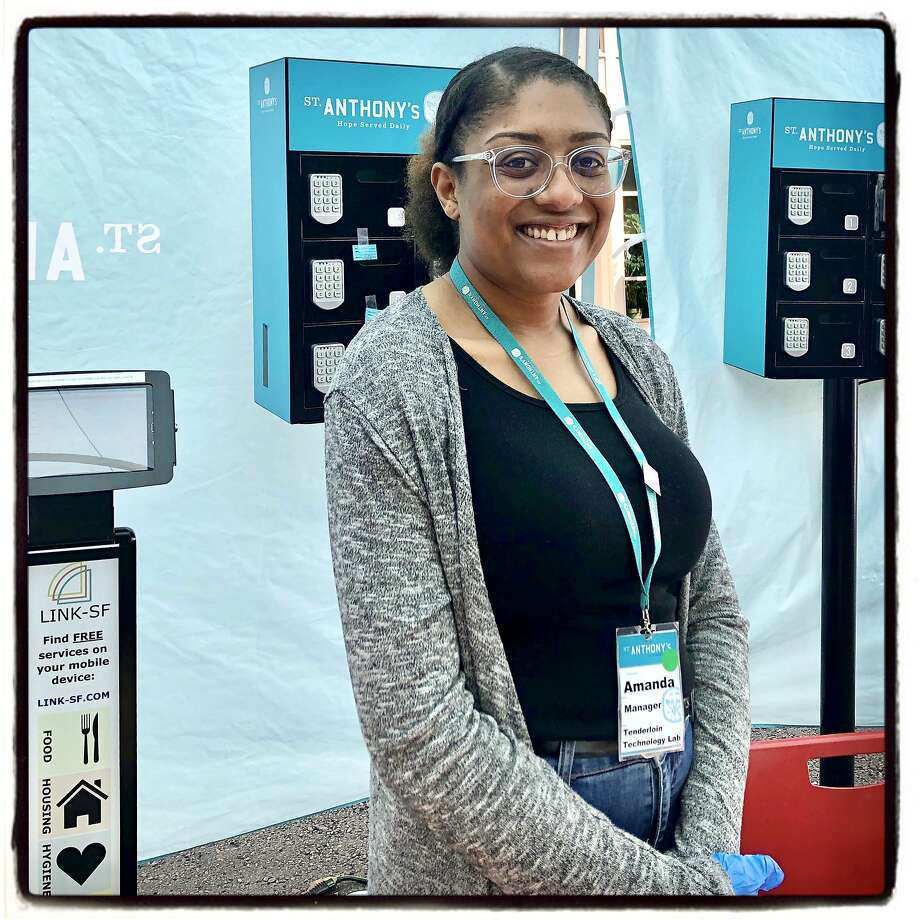 With in-person classes canceled because of coronavirus concerns, St. Anthony's Tenderloin Tech Lab manager Amanda Brown staffs a pop-up providing curbside WiFi access and device-charging stations on Golden Gate Avenue. March 25, 2020. Photo: Rachel Ball