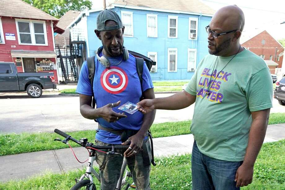 """Ashton P. Woods, right, gives Alonzo Lee a gift card in Houston. Woods launched a petition asking Texas Gov. Greg Abbott to suspend rent, mortgage and utility payments. """"For the most part, if you're black and brown, you're getting it a lot harder with the systemic racism and xenophobia,"""" Woods said. """"Now, we have a pandemic where people are scared to go to the doctor, let alone miss work, because they still have to pay their rent."""" Photo: David J. Phillip, STF / Associated Press / Copyright 2020 The Associated Press. All rights reserved"""