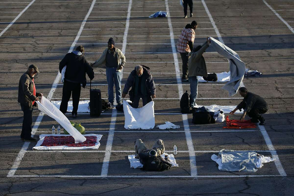 People prepare places to sleep in area marked by painted boxes on the ground of a parking lot at a makeshift camp for the homeless Monday, March 30, 2020, in Las Vegas. Officials opened part of a parking lot as a makeshift homeless shelter after a local shelter closed when a man staying there tested positive for the coronavirus. (AP Photo/John Locher)