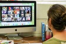 """A school principal sets up a """"Zoom"""" class on March 24, 2020, in Meridian, Miss. where Comcast is the major local broadband carrier. A week later, the Philadelphia-based giant indicated its Xfinity broadband network is handling increased daytime demands with plenty of extra capacity as any additional peak usage surfaces."""