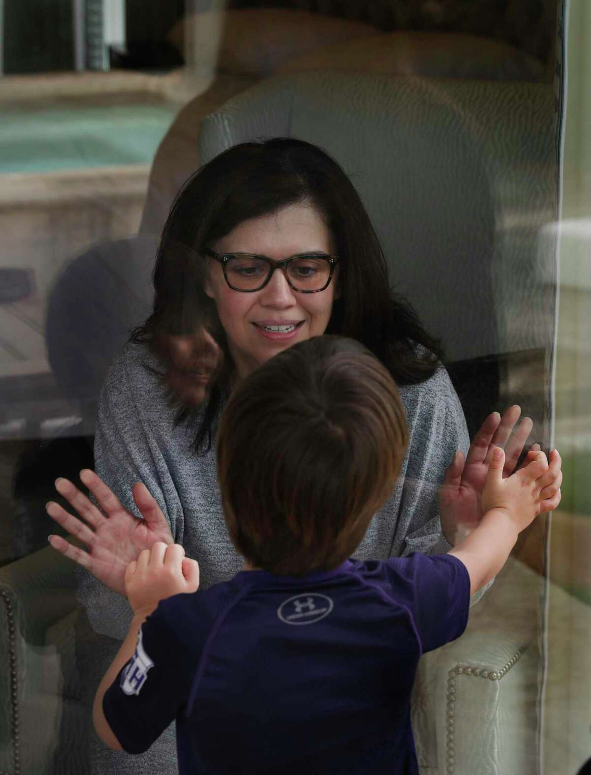 Justice Luz Elena Chapa greets her son Jose Chapa, 5, through a glass door. Chapa, Justice of the 4th Court of Appeals, was infected with the new coronavirus on a trip to Utah over Spring Break. She had a relapse this weekend.