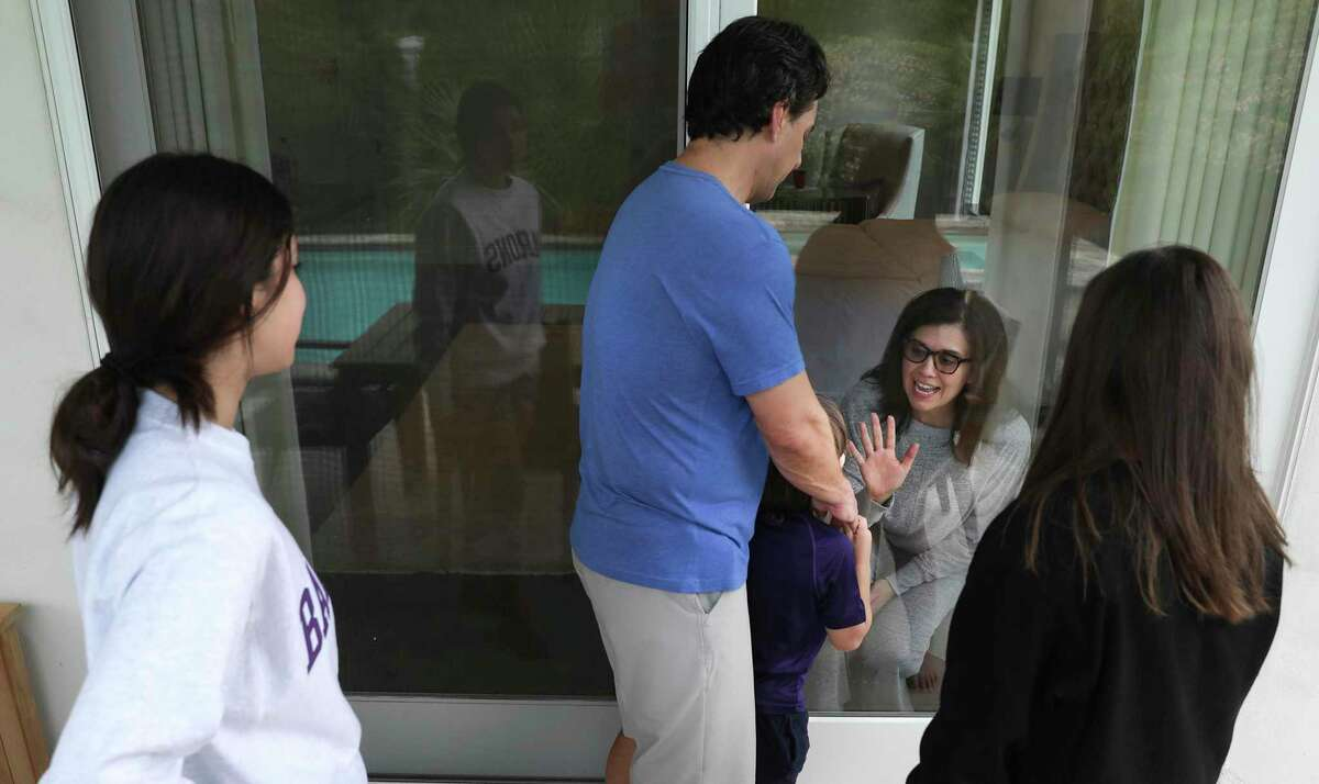 Justice Luz Elena Chapa, inside, greets her family daughter Luz Elena, left to right, husband Miguel Chapa, son Jose Chapa, and Natalia Chapa through the glass door that looks out to the patio.