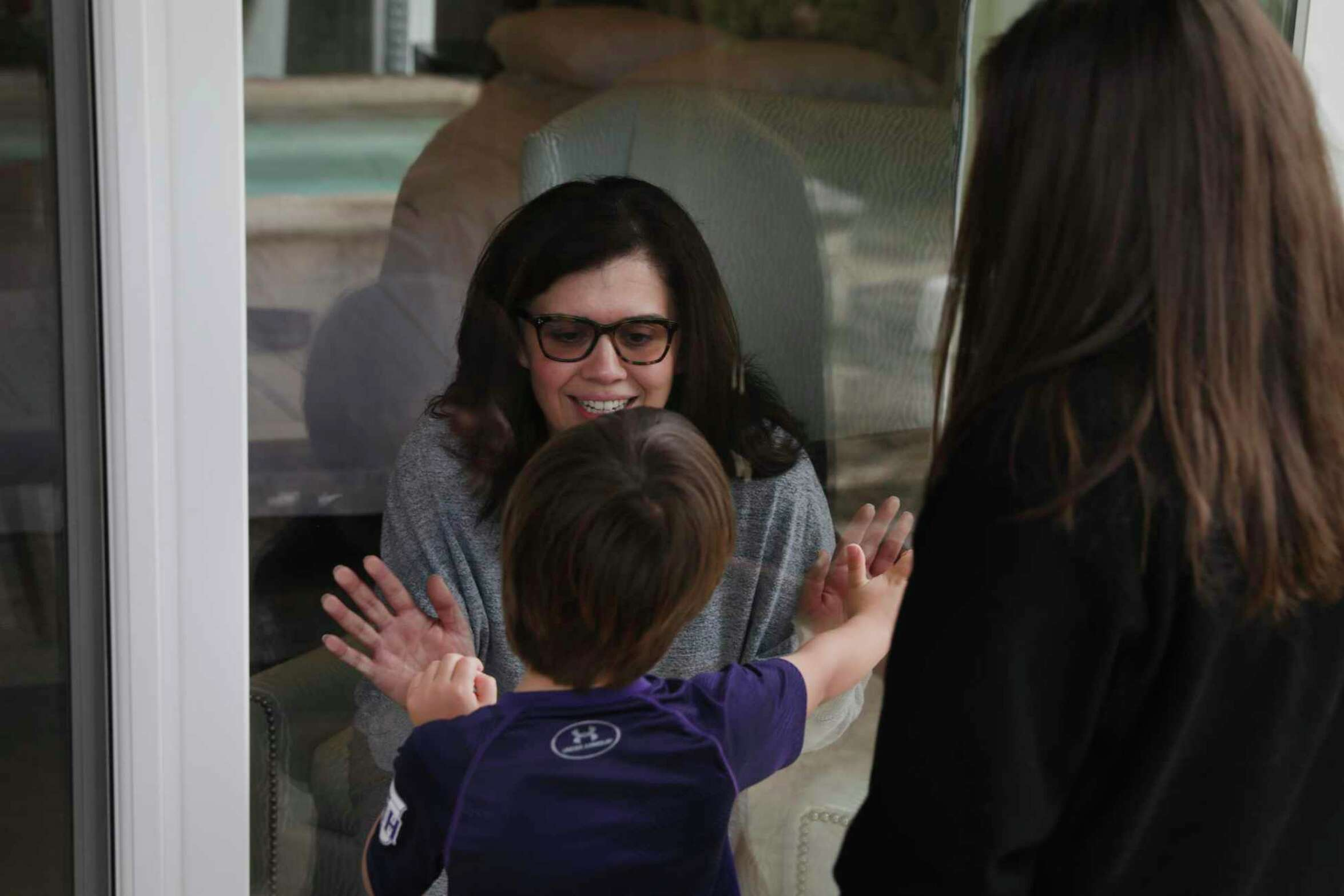 Justice Luz Elena Chapa greets her son Jose Chapa, 5, through a glass door with her daughter Natalia Chapa, right. Chapa, Justice of the 4th Court of Appeals was infected with the new coronavirus on a trip to Utah over Spring Break, on Monday, March 30, 2020.