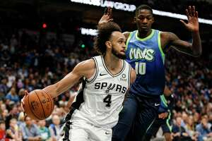 San Antonio Spurs guard Derrick White (4) looks for room against Dallas Mavericks forward Dorian Finney-Smith (10) during the second half of an NBA basketball game, Thursday, Dec. 26, 2019, in Dallas. Dallas won 102-98. (AP Photo/Brandon Wade)
