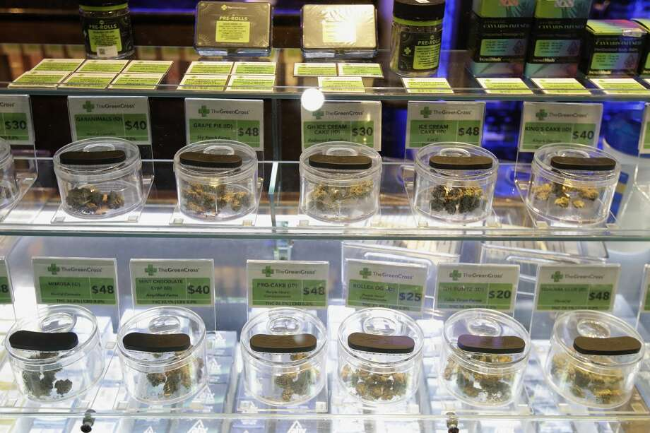 "Various marijuana buds for sale are displayed at The Green Cross cannabis dispensary in San Francisco, Wednesday, March 18, 2020. As about 7 million people in the San Francisco Bay Area are under shelter-in-place orders, only allowed to leave their homes for crucial needs in an attempt to slow virus spread, marijuana stores remain open and are being considered ""essential services."" Photo: Jeff Chiu/Associated Press / Copyright 2020 The Associated Press. All rights reserved"