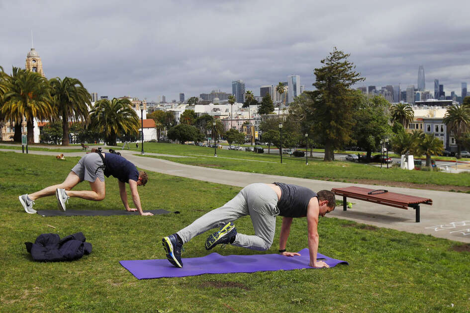Ty Walrod, foreground, and Mike McCormick keep their distance for coronavirus concerns while using a phone app to do a full body weight workout at Mission Dolores Park in San Francisco, Tuesday, March 24, 2020. Both Walrod and McCormick said they normally would work out in gyms.