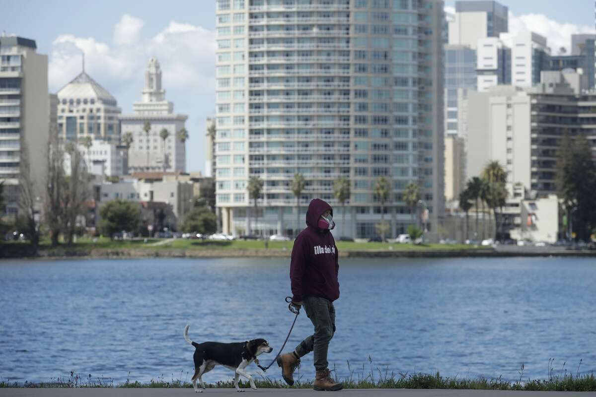 A man wears a mask while walking his dog in front of Lake Merritt in Oakland on March 26.
