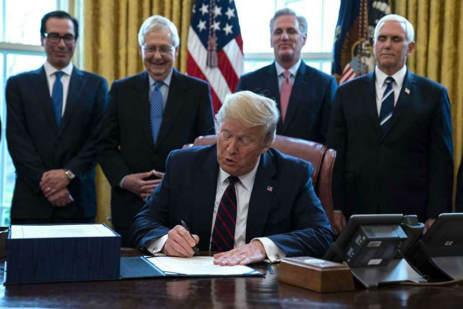 FILE - In this March 27, 2020 file photo, President Donald Trump signs the coronavirus stimulus relief package in the Oval Office at the White House in Washington, as Treasury Secretary Steven Mnuchin, Senate Majority Leader Mitch McConnell, R-Ky., House Minority Leader Kevin McCarty, R-Calif., and Vice President Mike Pence watch. Payments from a federal coronavirus relief package could take several weeks to arrive. Photo: (AP Photo /Evan Vucci, File)