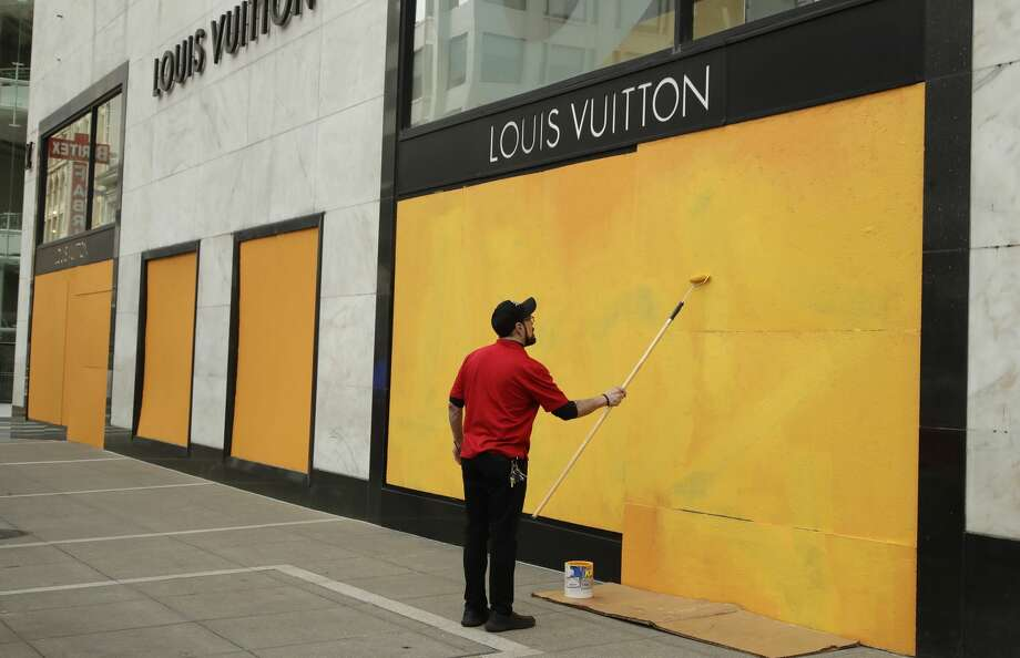 A worker paints over a boarded up Louis Vuitton storefront on Monday, March 30, 2020, in San Francisco. Photo: Ben Margot/Associated Press / Copyright 2020 The Associated Press. All rights reserved.