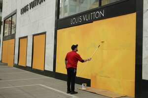 A worker paints over a boarded up Louis Vuitton storefront on Monday, March 30, 2020, in San Francisco.