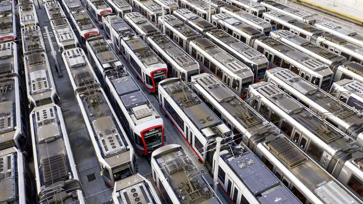 Muni light rail cars rest dormant at a Geneva Ave. storage and maintenance facility on Monday, March 30, 2020, in San Francisco.