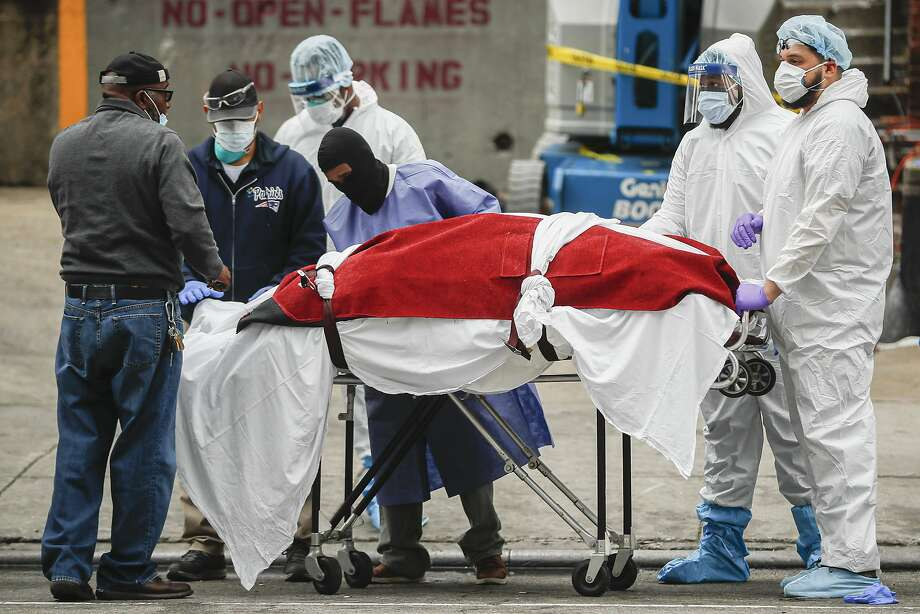 A body wrapped in plastic that was unloaded from a refrigerated truck is handled by medical workers wearing personal protective equipment at Brooklyn Hospital Center in Brooklyn. Photo: John Minchillo / Associated Press