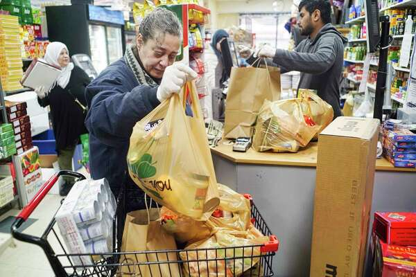 "Customer Camilia Eldidi from Harpersfield loads her purchases into a cart as she checked out at Aladdin Halal on Monday, March 30, 2020, in Albany, N.Y. Eldidi said that she travels to the store once every two weeks or sooner if she runs out of items she really needs. ""It is a wonderful store, the foods here remind me of my home"" Eldidi said. (Paul Buckowski/Times Union)"