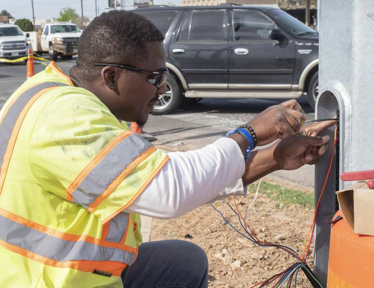 Anwar Culberson, with Willis Electric, attaches wiring as work continues 03/30/2020 as new lights are put in place at the Wadley and Big Spring intersection. Tim Fischer/Reporter-Telegram