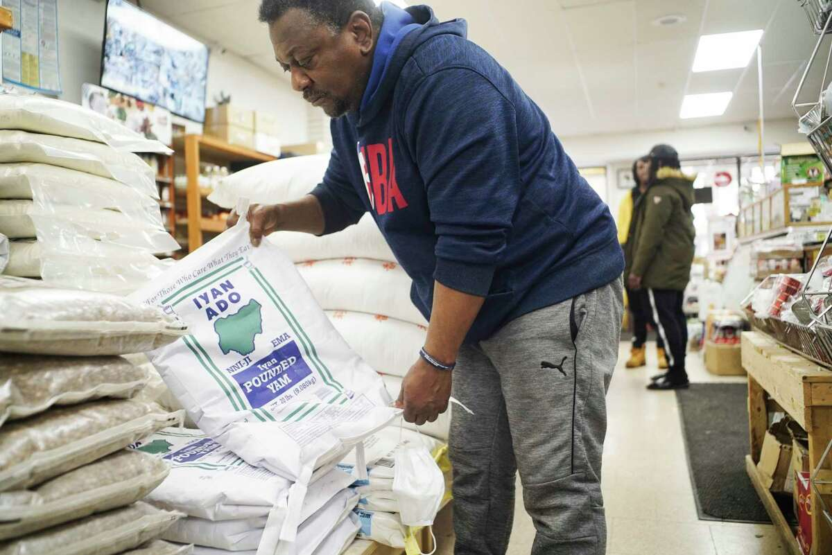 Kwasi Addo-Baffour, owner of Breakthrough African Market, stacks the remaining bags of yam flour on a shelf at his store on Monday, March 30, 2020, in Albany, N.Y. Addo-Baffour usually travels down to New York City to purchase products for his store, but because of the coronavirus he is not traveling and that is leading to some shortages of products. (Paul Buckowski/Times Union)