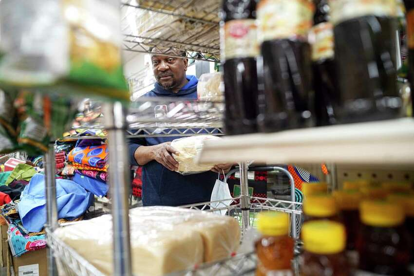 Kwasi Addo-Baffour, owner of Breakthrough African Market, holds one of the remaining loafs of African bread at his store on Monday, March 30, 2020, in Albany, N.Y. The coronavirus has stopped Addo-Baffour from traveling down to the New York City area when he would purchase products, like the African bread. (Paul Buckowski/Times Union)