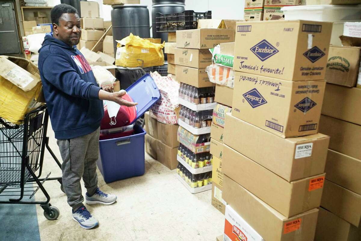 """Kwasi Addo-Baffour, owner of Breakthrough African Market, stands in his storage room at his store next to an stack of products recently delivered on Monday, March 30, 2020, in Albany, N.Y. Addo-Baffour said that he is having issues getting some products for his store, """"I ordered 20 bags of jasmine rice, they sent me one, I ordered 60 bags of sweet plantain chips, I got five, they tell me there is a shortage in the warehouse and the bigger stores are ordering a lot more"""", Addo-Baffour said. (Paul Buckowski/Times Union)"""