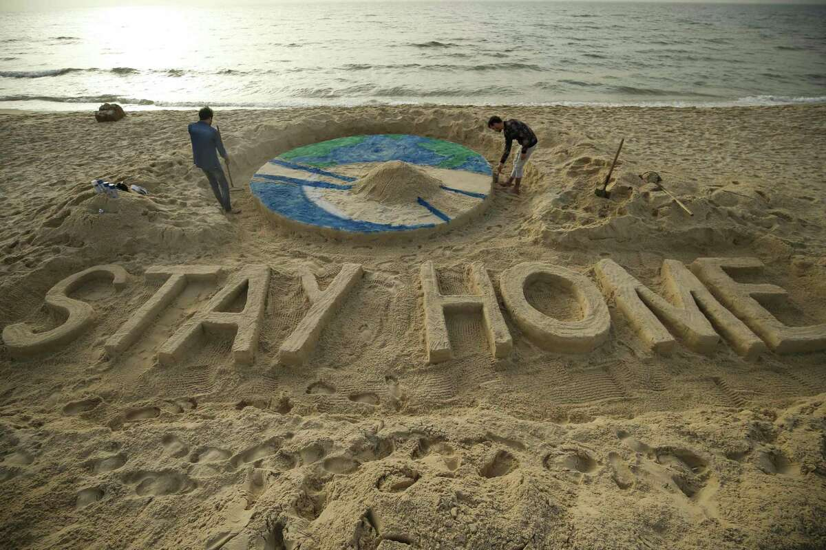 Palestinian artists work on a sand sculpture depicting the earth with a message reading