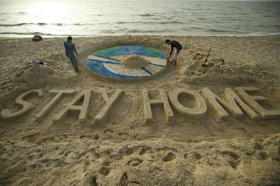 "Palestinian artists work on a sand sculpture depicting the earth with a message reading ""Stay Home"" along a beach in Gaza City during the COVID-19 coronavirus pandemic, on March 31, 2020. (Photo by MOHAMMED ABED / AFP) (Photo by MOHAMMED ABED/AFP via Getty Images) Photo: MOHAMMED ABED / AFP Via Getty Images / AFP or licensors"