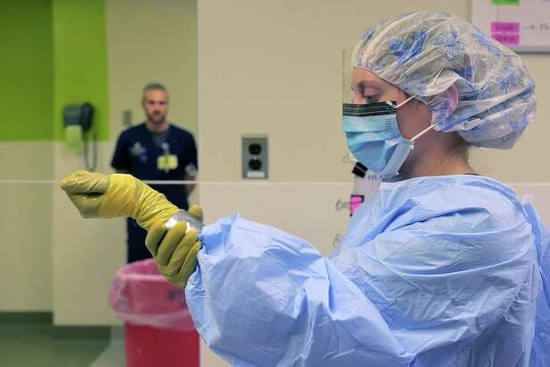 Samuel Gutner, a superior of the biocontainment unit watches lead clinical nurse Madeleine Steinberg rub hand sanitizer on her outer set of gloves which are sealed with tape as medical staff train at Johns Hopkins Hospital on Jan. 28, 2020. (Karl Merton Ferron/Baltimore Sun/TNS)