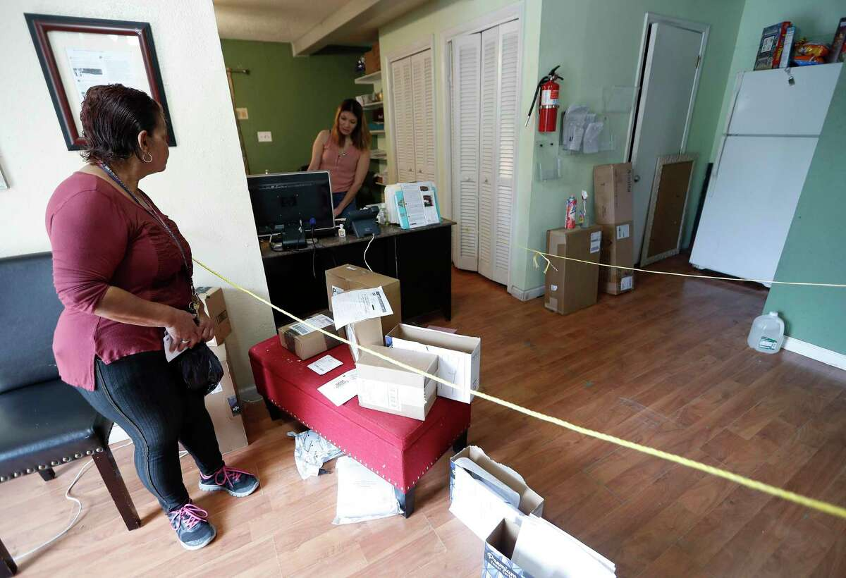 A tenant of the Westview Forest apartment complex stands across a barrier for safety inside of the leasing office at the in Houston, Monday, March 30, 2020. Landlord Jack Yetiv set up the two ropes to keep people at a safe distance due to the coronavirus pandemic.