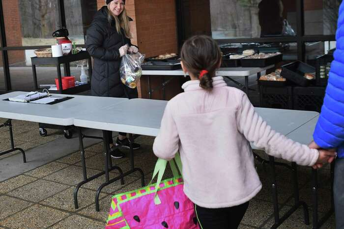 Tara McQuillen, an employee of Whitsons Culinary Group, school food provider for the Shelton school system, hands out bagged lunches and breakfasts for students outside Shelton High School in Shelton, Conn. on Tuesday, March 31, 2020.
