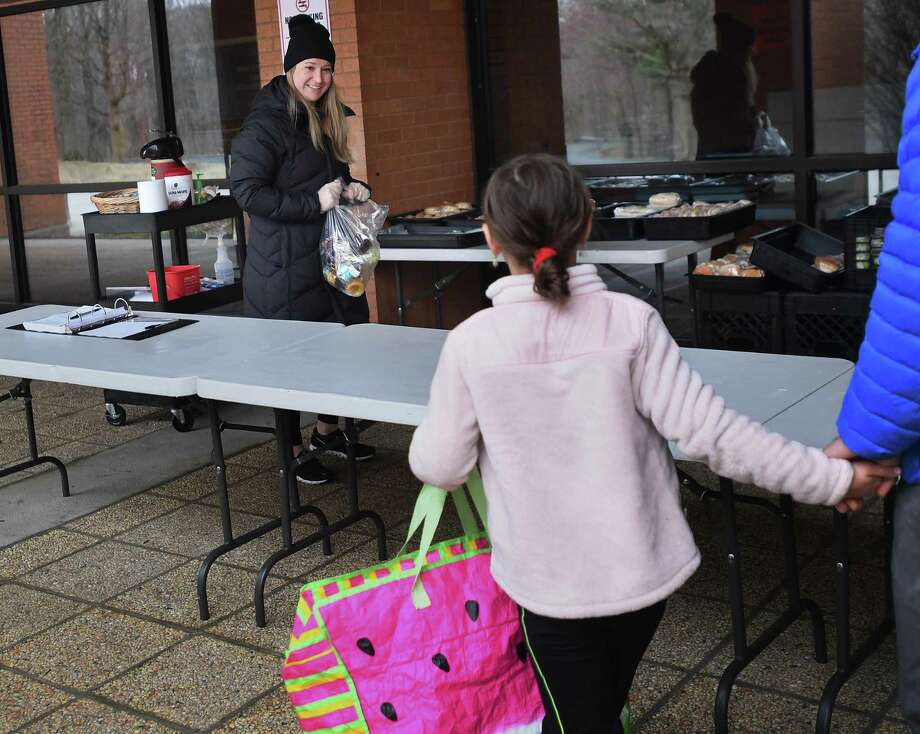 Tara McQuillen, an employee of Whitsons Culinary Group, school food provider for the Shelton school system, hands out bagged lunches and breakfasts for students outside Shelton High School in Shelton, Conn. on Tuesday, March 31, 2020. Photo: Brian A. Pounds / Hearst Connecticut Media / Connecticut Post