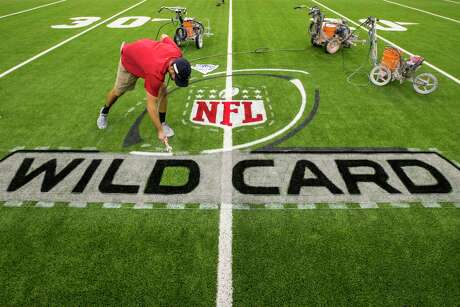 Kevin Hansen paints the Wild Card playoff logo on the field while preparing the turf for the AFC Wild Card playoff game between the Houston Texans and the Buffalo Bills at NRG Stadium on Friday, Jan. 3, 2020, in Houston.